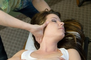 Dr. Carrie gives a female patient a chiropractic neck adjustment.