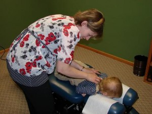 Dr. Carrie gives a young child a chiropractic adjustment.